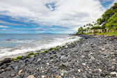 Maui black lava rocky beach with resort building. Hawaii. — Stock Photo