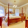 Romantic Bedroom with dressers and large wood bed. - 图库照片