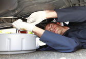Man changing car oil laying under vehicle. — Stock Photo