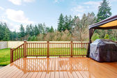 Backyard with wet deck, grill and fence. — Stock Photo