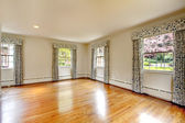 Large empty room with hardwood floor and curtains. Old luxury home. — Stock Photo