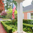 American old brick home with flag and classic garden. — Stock Photo