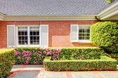 Brick red house with English garden and white window shutters. — Stock Photo