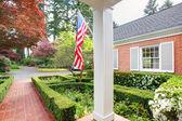 Americano vecchio mattone casa con bandiera e giardino classico. — Foto Stock