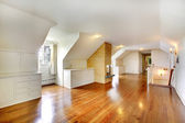 Large long attic room with fireplace. Empty with golden hardwood. — Stock Photo