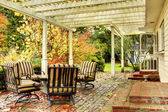 White house back porch with fall trees and chairs. — Stock Photo
