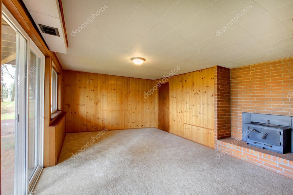 Vacía sala con paredes de panel de madera y chimenea de hierro ...