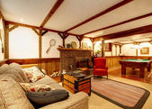 Quente rústica sala de estar mobilada com uma lareira e piscina tabl — Fotografia Stock