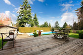 Wooden back poch overlooking swimming pool and trim — Stock Photo