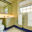 Bright yellow bathroom with blue tile floor — Stock Photo
