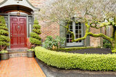 Classic brick house entrance with trim hedge — Stock Photo