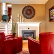 Stock Photo: Bright family room with electric fireplace and elegant red chair