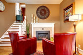 Bright family room with electric fireplace and elegant red chair — Stock Photo