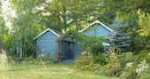 Flourishing farm backyard with sheds and garden house — Stock Photo