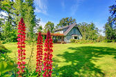 Big farmhouse with beautiful flowerbed — Stock Photo