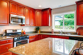 Bright kitchen room with cherry wood storage combination — Stock Photo