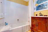 Refreshing bathroom with antique wood cabinet — Stock Photo