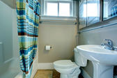 Cozy bathroom with striped curtains — Stock Photo