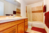Warm colors bathroom with red towels and rug — Stock Photo