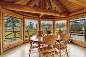 Beautiful dining room in log cabin house — Stock Photo