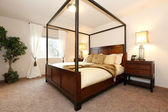 Warm beautiful bedroom with a high posts bed — Stock Photo