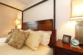 High posts bed with a beautiful beige bedding and nightstand. Cl — Stock Photo