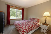 Bedroom with red bed and brown walls — Stock Photo