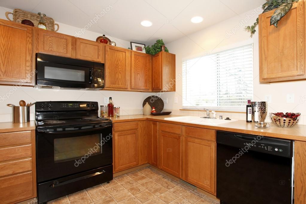 Marrone armadi da cucina con elettrodomestici neri — foto stock ...
