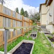 Stock Photo: Small backyard garden bed wih wooden trellis and grid