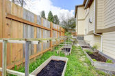 Small backyard garden bed wih wooden trellis and grid — Stock Photo