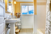 Yellow and white bathroom with a window — Stock Photo
