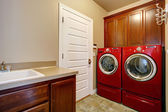 Laundry room with modern red appliances — Stock Photo