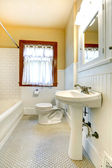 Yellow and white bathroom with window — Stock Photo