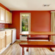 Red dining room with rustic table and bench — Stock Photo #47642073