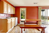 Red dining room with rustic table and bench — Stock Photo