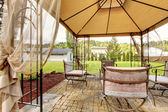 Backyard gazebo with antique chairs — Stock Photo