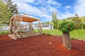 Backyard with gazebo and decorative tree — Stock Photo