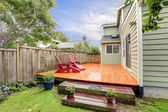 Wooden deck with red chairs — Stock fotografie