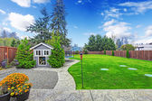 Fenced backyard with lawn and shed — Stock Photo