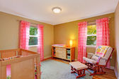 Nursery room with pink ruffle curtains — Stock Photo