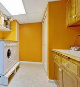 Bright yellow laundry room interior — Stockfoto