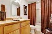 White bathroom interior with honey vanity cabinet — Stock Photo