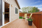 Cozy small backyard with wooden walkout deck — Stock Photo