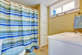 Ivory bathroom interior with stripped blue curtain — Stock Photo