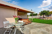 House exterior. Backyard deck with glass top table and chairs — Stock Photo