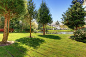 Residential complex backyard garden with pond, trees and sitting — Stock Photo