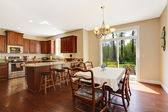 Spacious kitchen room with dining area and walkout deck — Stock Photo