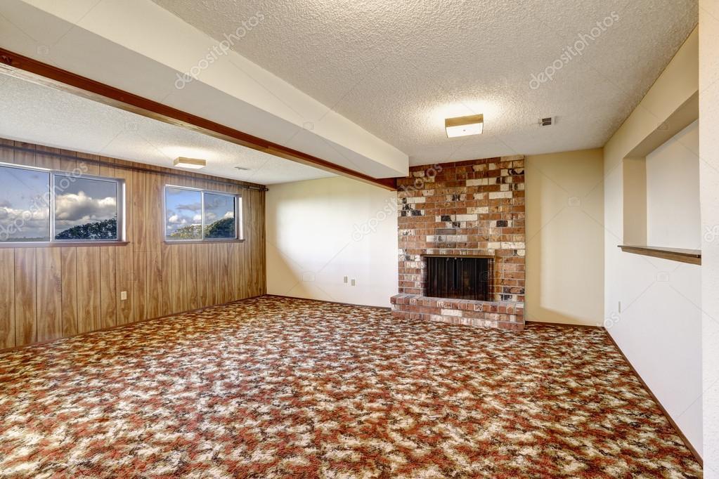 Vazia sala de estar com lareira de tijolos e piso de tapete ...
