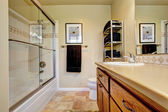 Bathroom wtih wooden vanity cabinet screened tub — Stock Photo