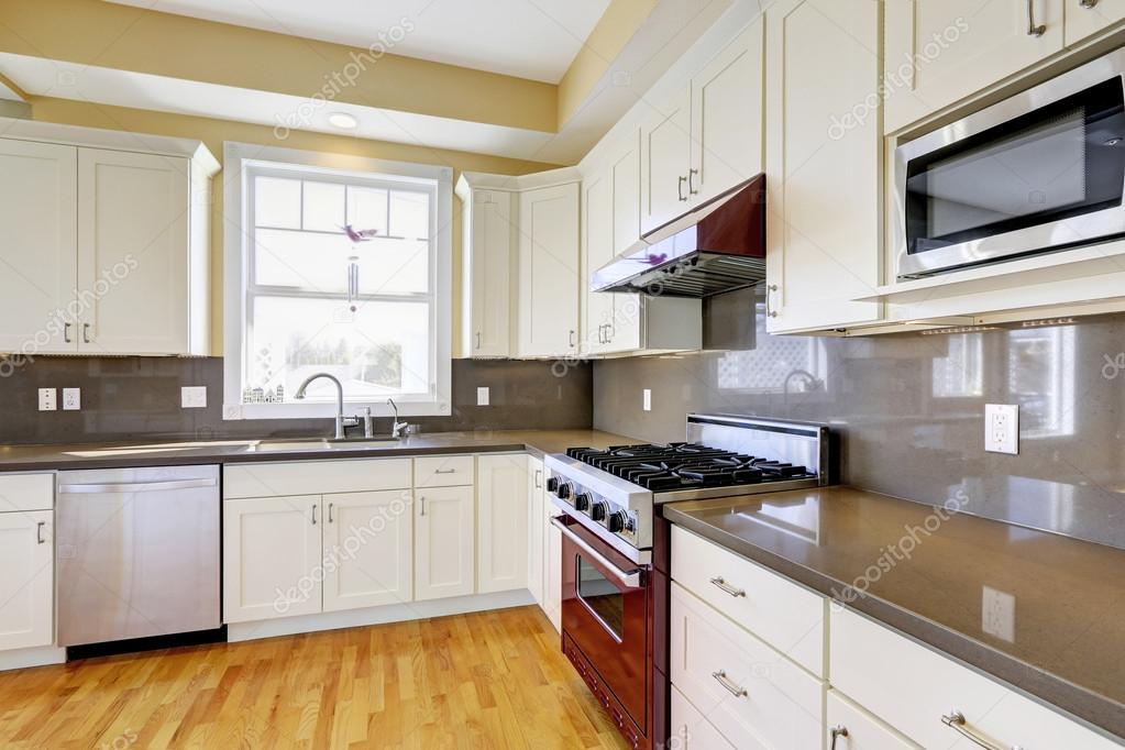 Witte keuken met donkerrood fornuis en grijze aanrechtbladen ...